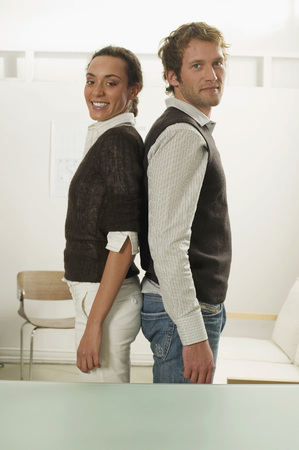 Young Couple Standing Back To Back, Side View, Portrait LANG_EVOIMAGES