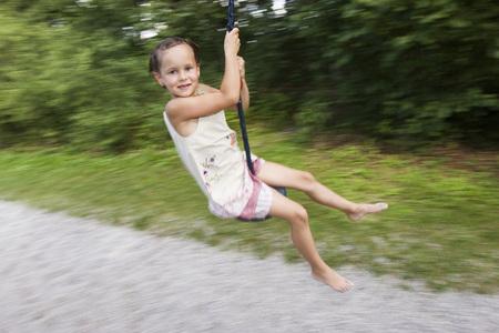 Girl (7-9) Sitting On Swing, Blurred Motion