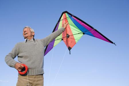 in low spirits: Senior Man Flying Kite, Smiling, Low Angle View LANG_EVOIMAGES