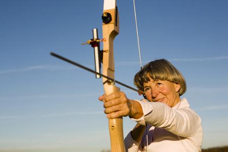 adentro y afuera: Mujer adulta mayor con arco y flecha