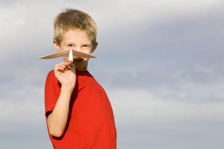 Boy (10-12) Holding Paper Plane LANG_EVOIMAGES