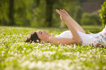 Young Woman Lying In Meadow, Holding Mobile Phone, Side View LANG_EVOIMAGES