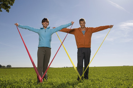 Young Couple Exercising With Resistance Band LANG_EVOIMAGES