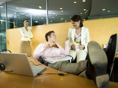 Couple Having Lunch In Office, Woman Watching