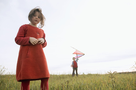 Girl (7-9) Standing In Meadow, Boy (10-12) Holding Kite In Background LANG_EVOIMAGES