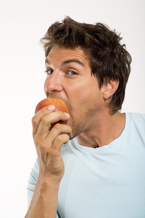 Young Man Eating Apple,Portrait,Close-Up LANG_EVOIMAGES