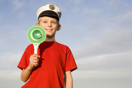 Boy (10-12) Wearing Police Cap, Holding Green Sign LANG_EVOIMAGES