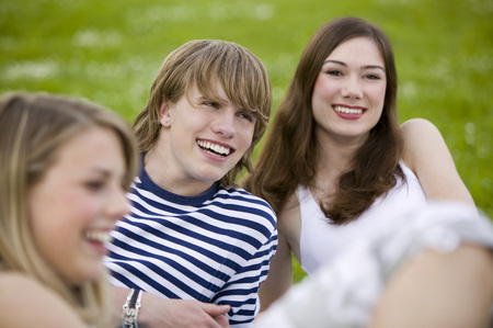Young People Sitting In Meadow, Smiling
