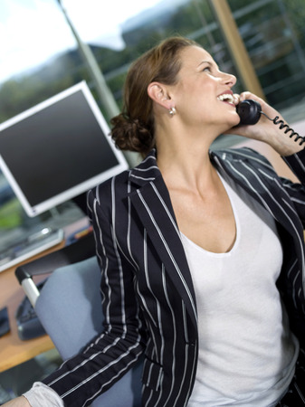 Businesswoman Using Telephone In Office, Laughing, Close-Up