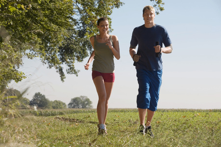 Young Couple Jogging In Field