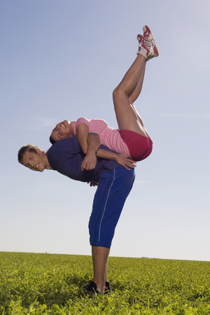 complete: Young Couple Exercing Gymnastic On Meadow, Side View