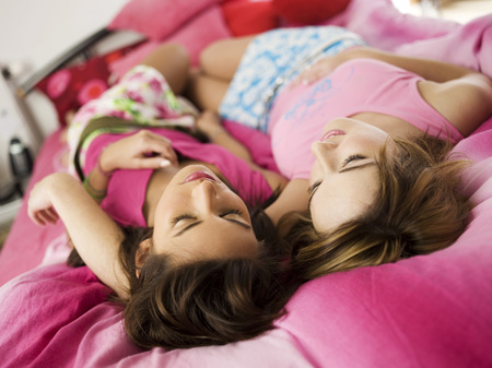 closed community: Two Teenage Girls Lying On Bed LANG_EVOIMAGES