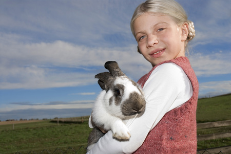 Girl (7-9) Holding Rabbit In Arms, Portrait, Close-Up