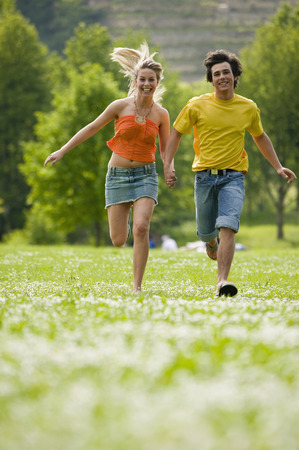 Young Couple Running In Meadow With Hand In Hand LANG_EVOIMAGES