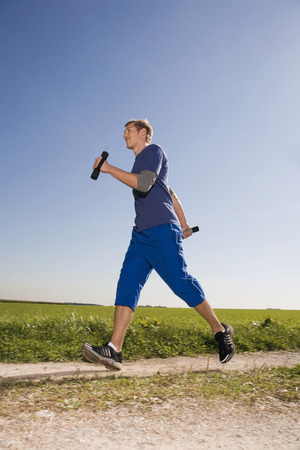 run way: Young Man Jogging, Carrying Dumbbells LANG_EVOIMAGES