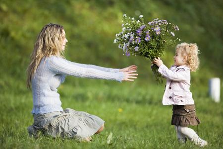 arrodillarse: Hija que da a madre un montón de flores, vista lateral