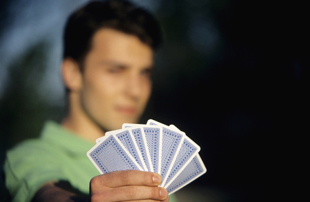 Young Man Holding Playing Cards, Focus On Cards At Foreground, Close-Up