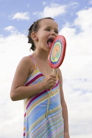 Girl (7-9) Holding Big Lollipop