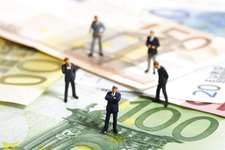 Figurines Standing On Euro Banknotes LANG_EVOIMAGES
