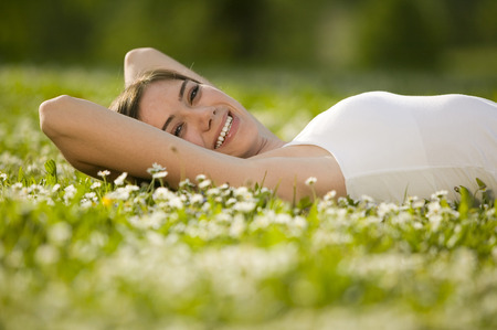 Young Woman Lying In Meadow, Smiling, Portrait