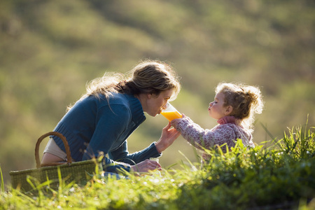 Mother Sitting With Daughter In Meadow, Drinking From Daughters Glass