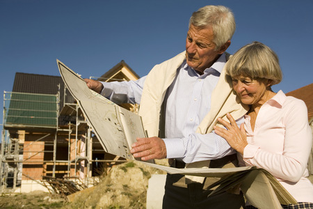 Senior Couple Holding Plan In Front Of Partially Built House LANG_EVOIMAGES