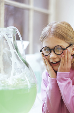enquiring: Girl (8-9) In Chemical Lab, Looking At Flask With Head In Hands