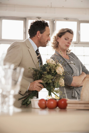 Mature Couple In Kitchen With Flower Bouquet