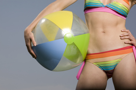 Young Woman In Bikini Holding Beach Ball LANG_EVOIMAGES