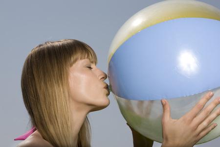 eye ball: Young Woman Blowing Up Beach Ball, Portrait