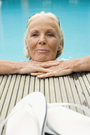 sandalias: Germany, Senior Woman Resting On Edge Of Pool, Smiling LANG_EVOIMAGES
