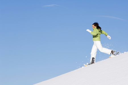 Woman With Snowshoes Running Downhill