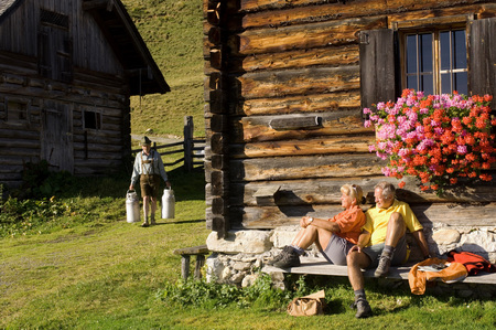 Mature Couple Sitting In Front Of Alpine Hut, Farmer Carrying Milkcans