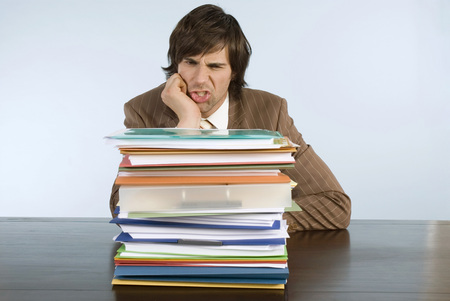 burned out: Man Sitting On Desk With Stack Of Files, Hand On Chin LANG_EVOIMAGES