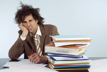 Businessman Sitting On Desk With Stack Of File, Head In Hands, Portrait