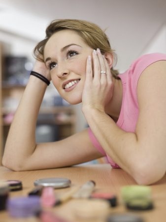 Young Woman Leaning On Table With Cosmetics