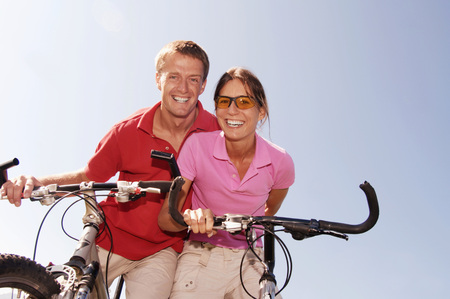 Young Couple On Bicycle, Smiling, Low Angle View, Portrait LANG_EVOIMAGES