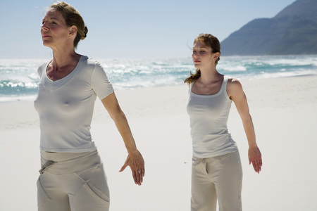 closed community: Two Women Exercising Yoga On Beach LANG_EVOIMAGES
