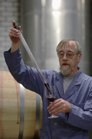 Man Testing Wine From Cask LANG_EVOIMAGES