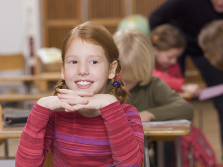 Girl (4-7) In Classroom, Smiling, Head On Hands, Close-Up