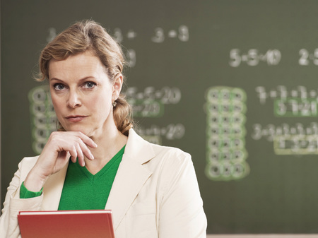 Woman Standing By Blackboard, Holding Book, Close-Up, Portrait LANG_EVOIMAGES