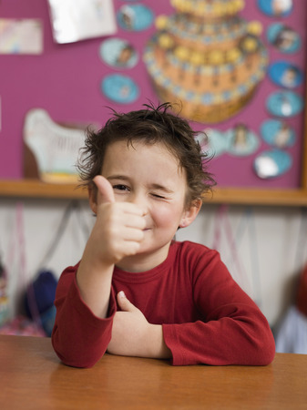 Boy (4-5) Sitting At Desk And Winking, Thumbs Up, Portrait LANG_EVOIMAGES