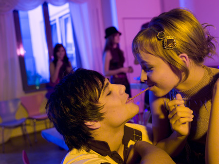 Young Couple On Party With Pretzel Sticks LANG_EVOIMAGES