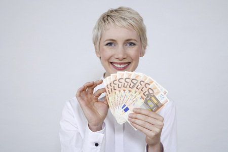 Young Woman Holding Money, Portrait LANG_EVOIMAGES