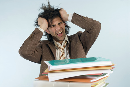 Man Sitting At Desk With Piled Files, Shouting LANG_EVOIMAGES