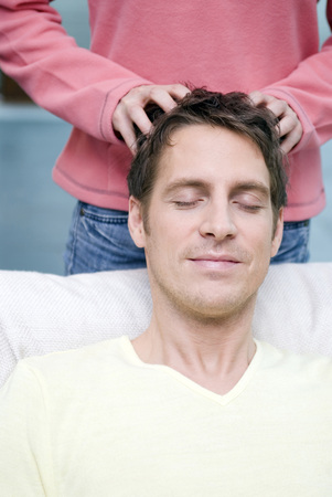 Young Woman Massaging Head Of Her Boyfriend LANG_EVOIMAGES