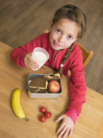 Girl (4-7) Holding Glass Of Milk And Lunch Box By Desk, Elevated View LANG_EVOIMAGES