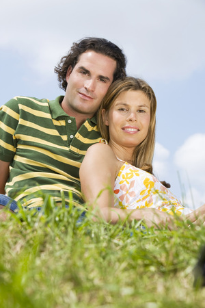 Couple Sitting In Meadow, Close-Up