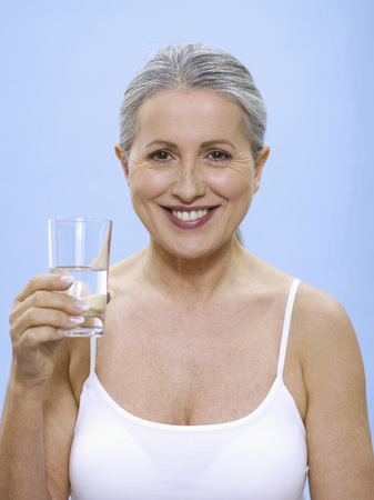 Senior Woman Holding Glass Of Water, Portrait LANG_EVOIMAGES