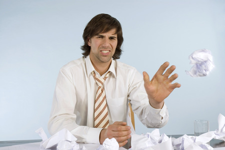 Businessman Sitting On Desk Throwing Paper Ball